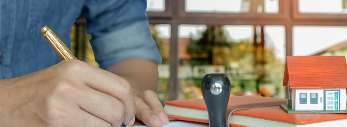Pen handles signed documents with rubber stamp.model houses, notebook on the table.